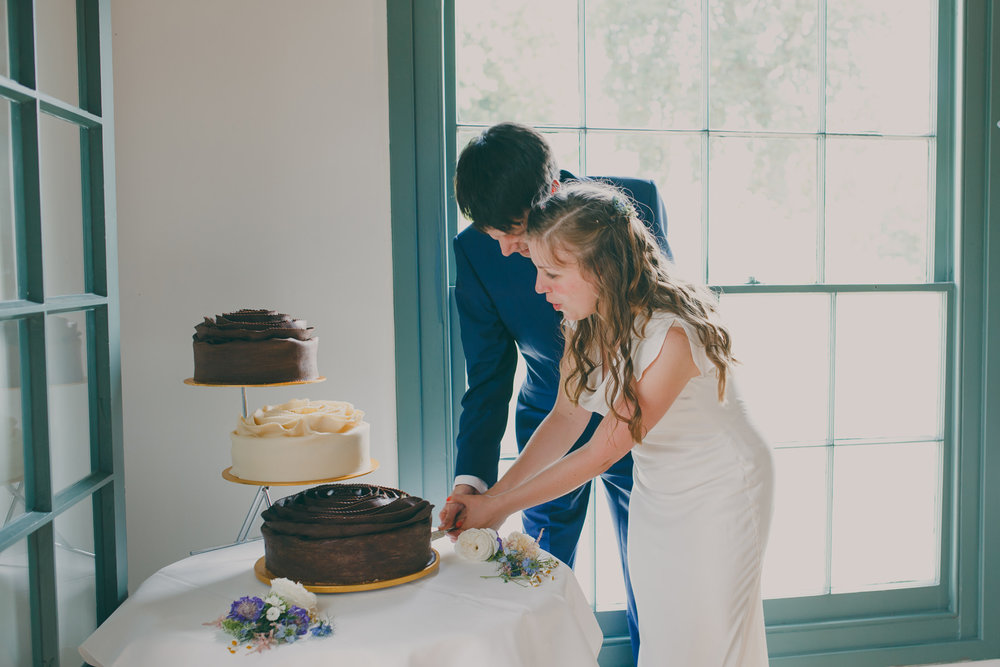 64 bride and groom cut wedding cake The Wharf.jpg