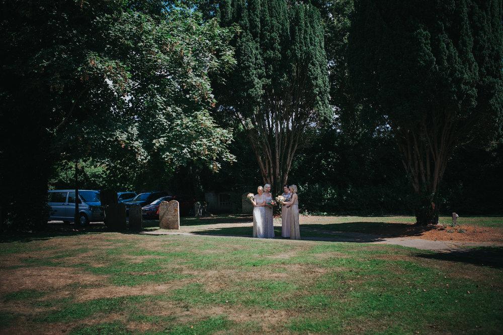 88 bridesmaids waiting bride in churchyard.jpg