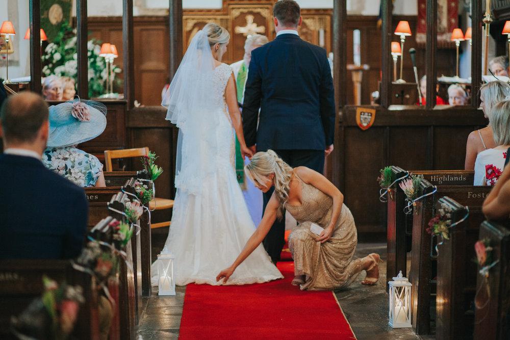 95 bridesmaid fixing brides train church wedding.jpg