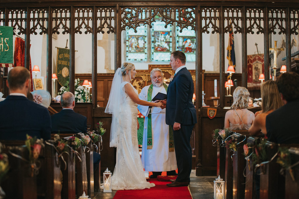102 groom holds brides hand marriage ceremony St Georges church .jpg