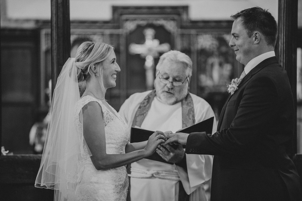 107 bride and groom exchanging rings church wedding ceremony West Sussex.jpg