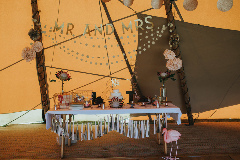131 Mr and Mrs gold sign cake table tipi Knepp Castle reportage wedding photographer.jpg