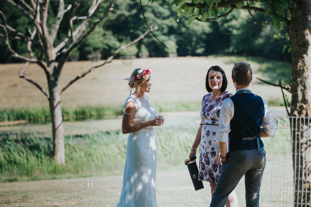190 Knepp Castle bride chatting to guests  reportage wedding photographer.jpg