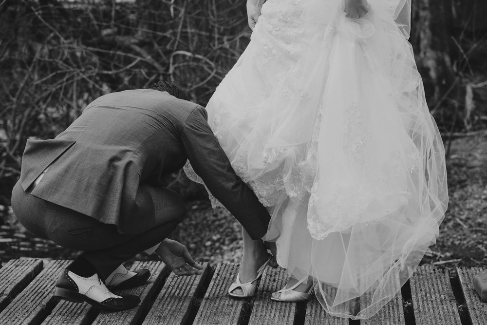 Groom doing up brides sandal wedding reportage photographer.jpg