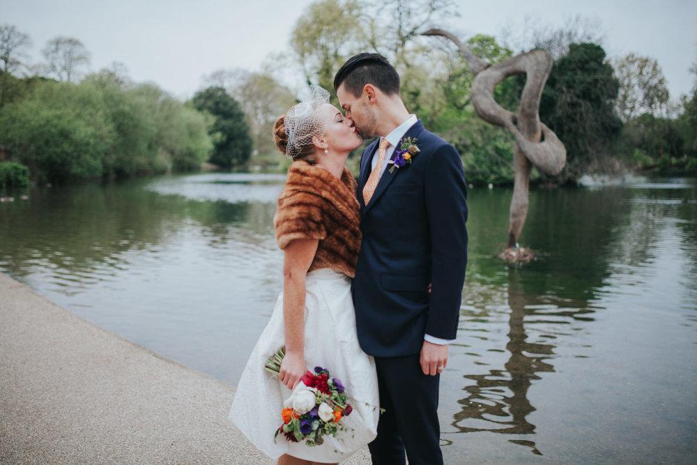 156-just-married-quirky-bride-groom-kissing-lake-Victoria-Park-Londesborough-Pub-wedding.jpg