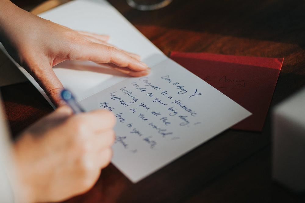 292  wedding guest writing card under table.jpg