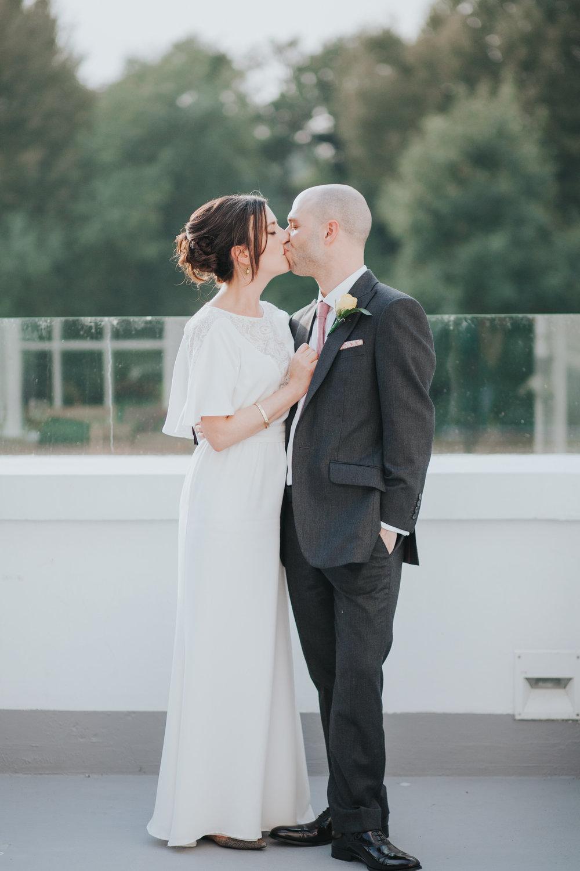308 London bride groom kissing sunset balcony.jpg
