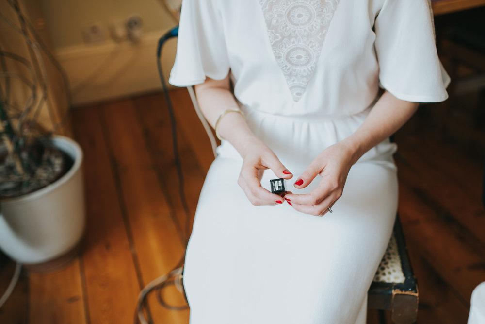 bride holding lipstick getting ready Minna wedding dress.jpg