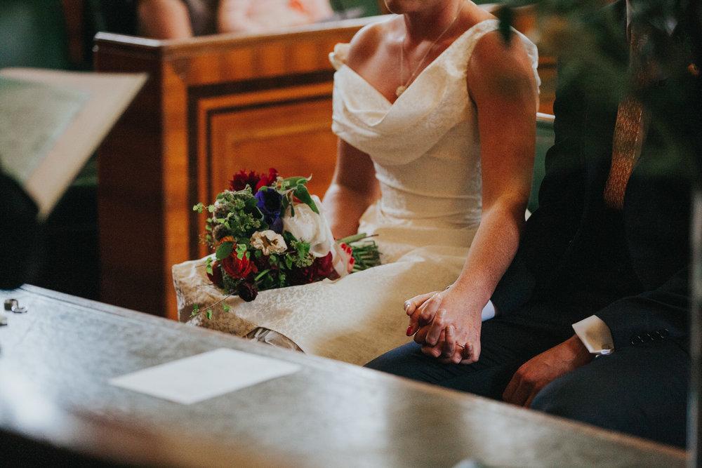 bride-holding-grooms-hand-during-ceremony-wedding-Hackney-alternative-photographer-.jpg
