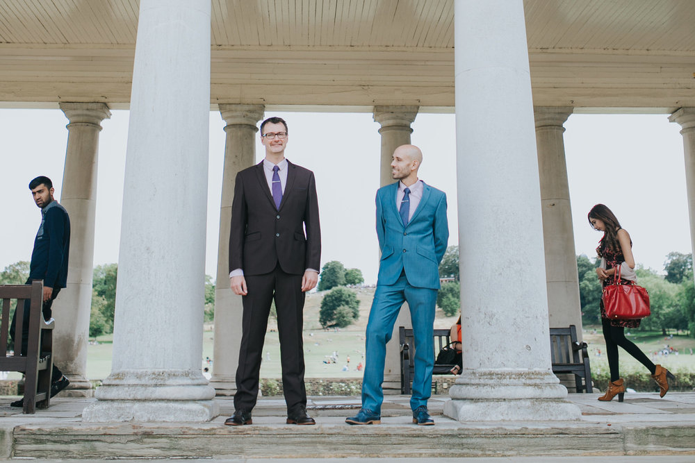 documentary style wedding portrait two grooms and photobombers Greenwich collonades.jpg
