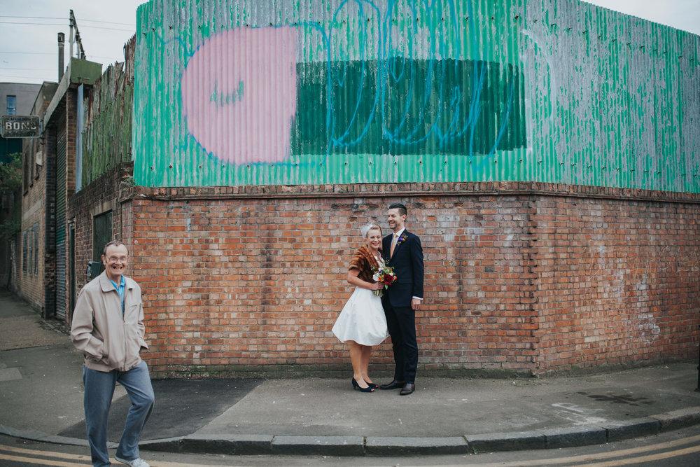 East End wedding quirky-bride-groom-grafitti photobomb.jpg