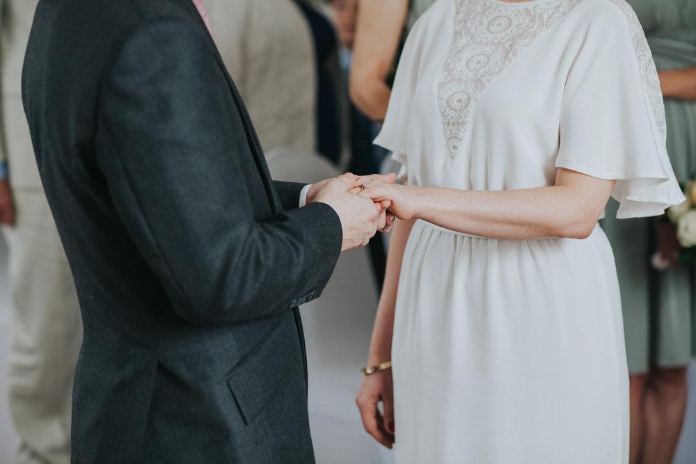 groom places wedding ring brides finger.jpg