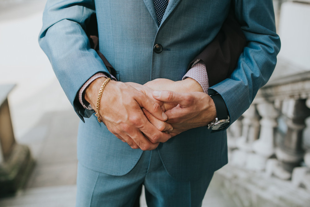 hands two grooms holding each other hands.jpg