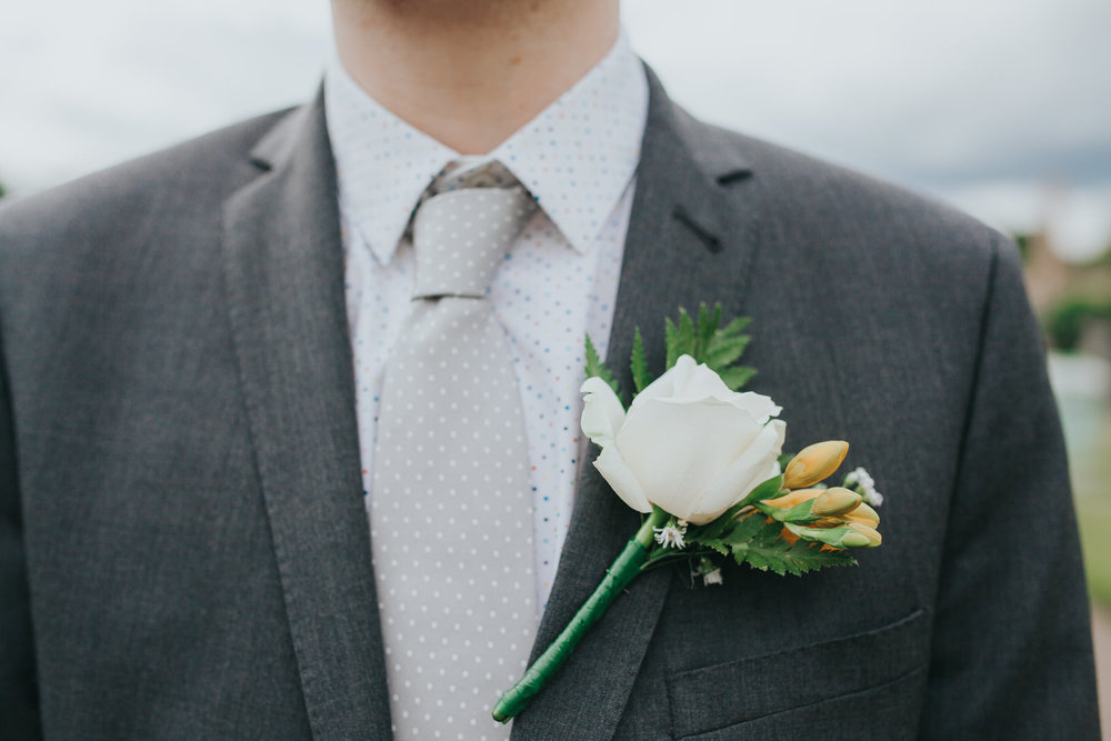 white rose buttoneire groom Brompton Cemetery.jpg