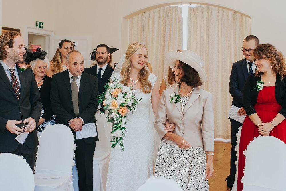 43 bride walks down aisle mother Pembroke Lodge wedding photographer.jpg