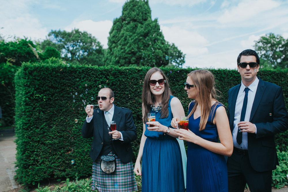 93 Pembroke Lodge South Lawn wedding guests blowing bubbles.jpg