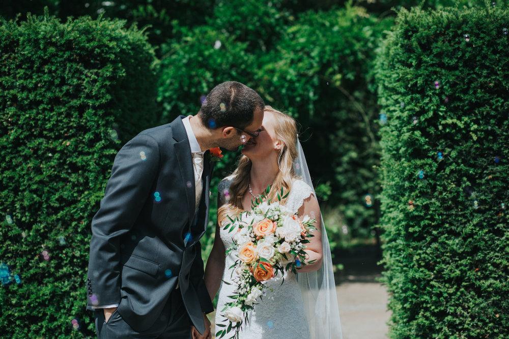 102 first kiss bubble confetti Pembroke Lodge South Lawn wedding photography.jpg