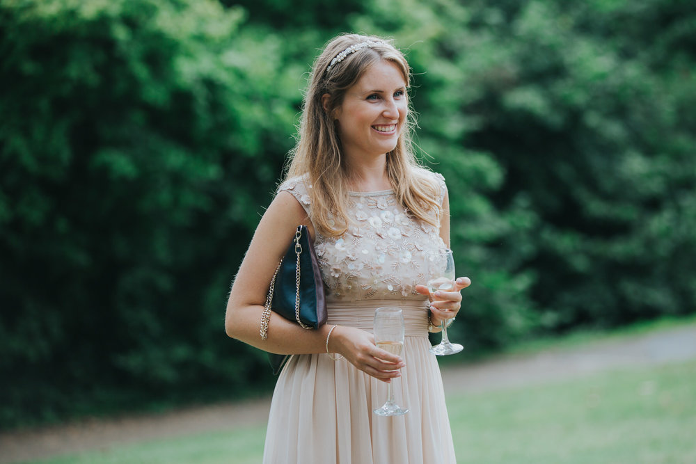 399 bridesmaid holding two glasses champagne Pembroke Lodge.jpg