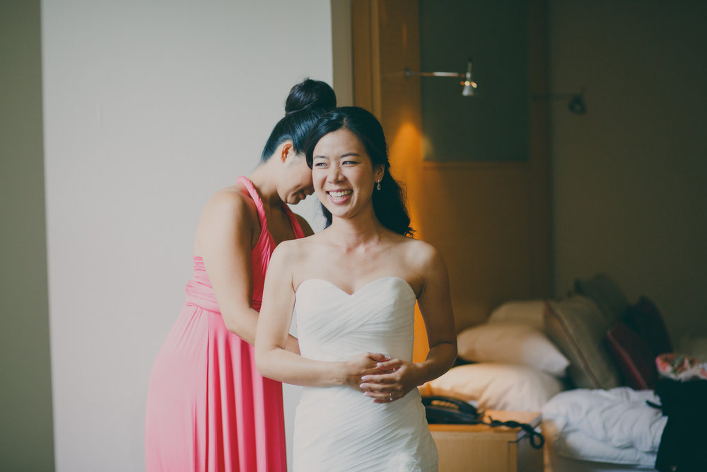 60 lovely moment bridesmaid zipping bride's dress.jpg