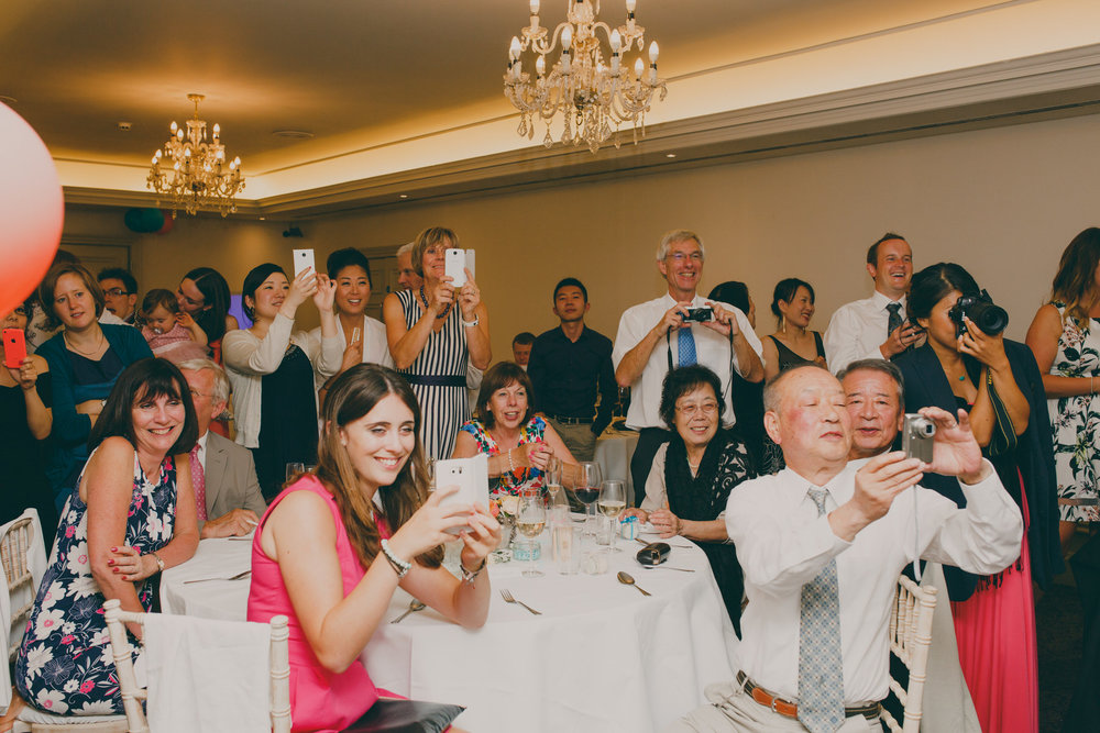 586 guests taking photos cutting of cake Surrey wedding photographer.jpg