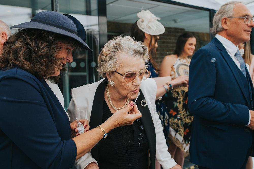 The Bingham Wedding Richmond-groom bride guests blowing bubbles balcony.jpg