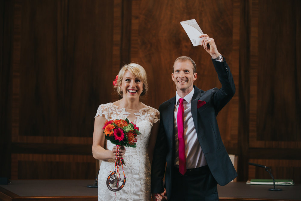 Groom holding marriage certificate stoke Newington Town hall wedding photographer.jpg