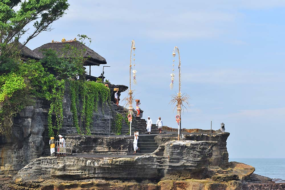 Local worshippers climb the temple steps to present their hand-made offerings to deceased relatives and gods.
