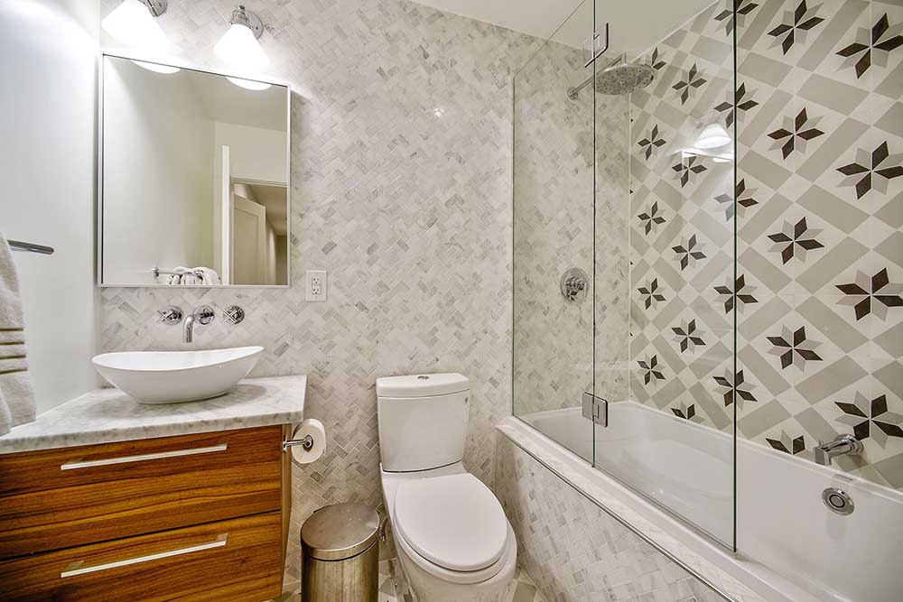 We chose patterned cement tiles for the floors and shower wall, and small Calacatta marble tiles in a herringbone design for the remaining walls. I couldn't find a vanity that was right for this space - so I bought the drawers, marble slab, and sink all separately, and had them assembled into this vanity.