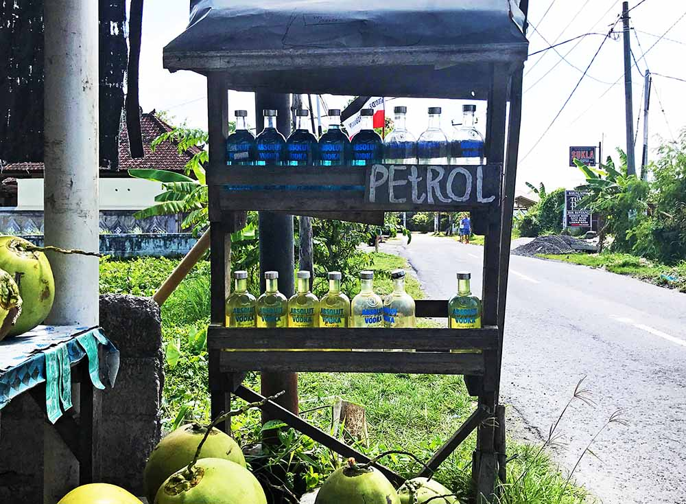 A road side petrol (gasoline) vendor. Notice the whole fresh coconuts also for sale!