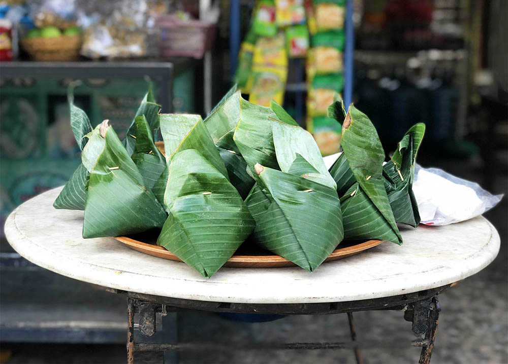Balinese 'fast food' for sale at a roadside shop, wrapped in banana leaves.