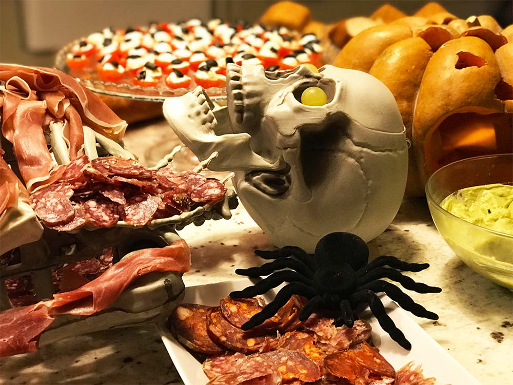 A grotesque skeleton of charcuterie, and a platter of 'bloodshot eyeballs' behind (made from cherry tomatoes, mozzarella cheese and black olives).