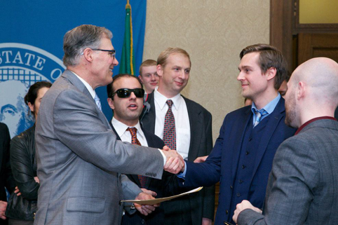 Olson, right, shakes hands with Gov. Jay Inslee. Photo republished from    Seattle Weekly   .