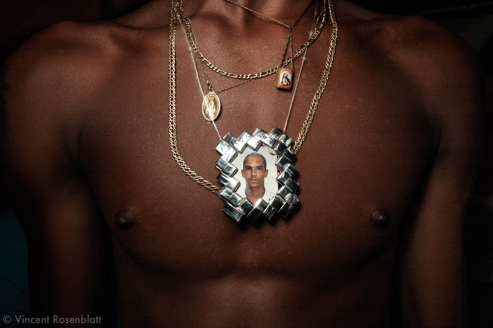 Pendant representing a deceased friend. Baile Funk in Morro do Turano slum. Rio de Janeiro, 2006..The Funk carioca movement is fashion and look as well  : The boys show off their muscles and naked torsos, adorned with chains and tattoos, accessories which will make the difference during the ball.  Girls will look after their bikini marks, which will appear above mini-skirts or micro-shorts.  Everything is worth to draw attention! .