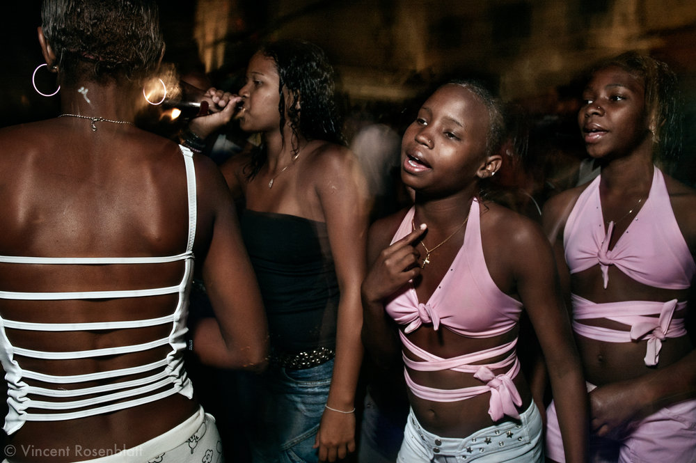 "Two sisters attend the Baile in the favela Mineira, Rio de Janeiro..As a contrast to rap the ""baile funk"" in the favela is a stage for discipline and respect, being a girl or a boy, a dancer or a junkie. It's a moment of dignity, pride, collective choreographic creations .No boy will approach a girl during a ball unless invited. The explicit lyrics of the ""baile"" contrast with the absence of vulgarity, the beauty of gestures, dance movements. ."
