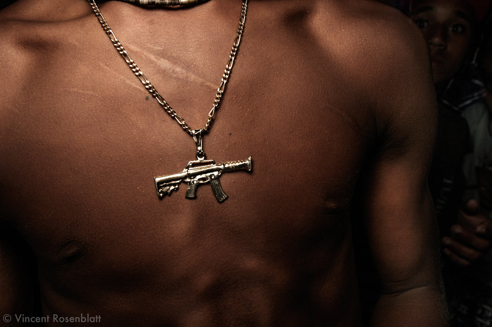 """Submachine gun pendant ,  Baile of Curtisomrio soundsystem, downtown Rio de Janeiro.  A hint to the omnipresence of weapons on favelas' territory..The Funk carioca movement is fashion and look as well : the boys try and identify themselves to the gangs' """"warriors"""" who dominate Rio's favelas as to attract the girls' attention and assert oneself.."""