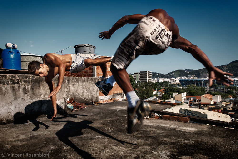 """Vitor Hugo, Diego, Anderson and Heverton, """"Muleks 100 limits"""" (""""boys without limits"""") are training on the rooftop of Diego's house, on the heights of Mangueira favela . They rehearse almost every day, and perfect their choreographies, hoping to have success on the carioca funk scene and get a better life. Down the hill, the Maracanã stadium."""