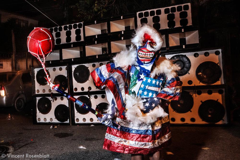 Yong Bate-Bola kid wearing an USA inspired fantasy  at the Faz Quem Quer favela, North Zone of Rio de Janeiro, Carnival 2018. Baile Funk soundsystem in the background, as Funk Carioca is the main soundtrack for the Bate-Bola.