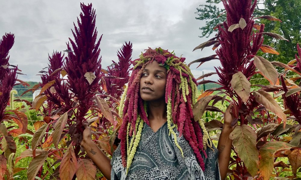 "Queen Mariama models the ""Love Lies Bleeding"" amaranth headdress standing in Kira's amaranth field."