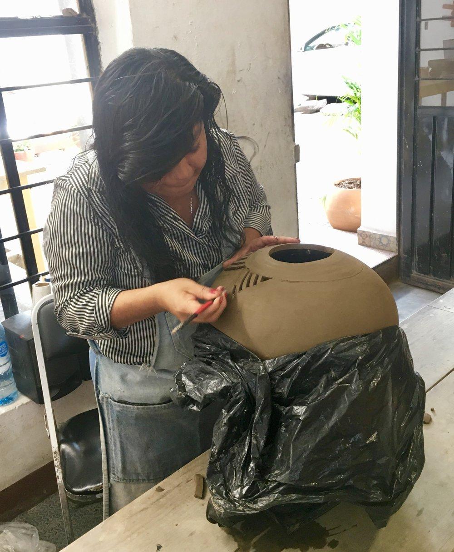 Woman carving clay pottery Oaxaca Mexico