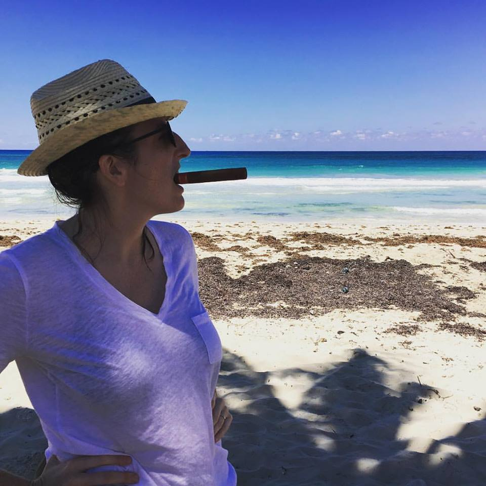 Straw hat, cigar and sea at Guanabo beach.