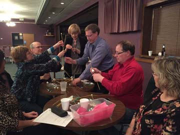 Harvey, N.D., Chamber of Commerce members working together to build the tallest possible tower with their pooled supplies.