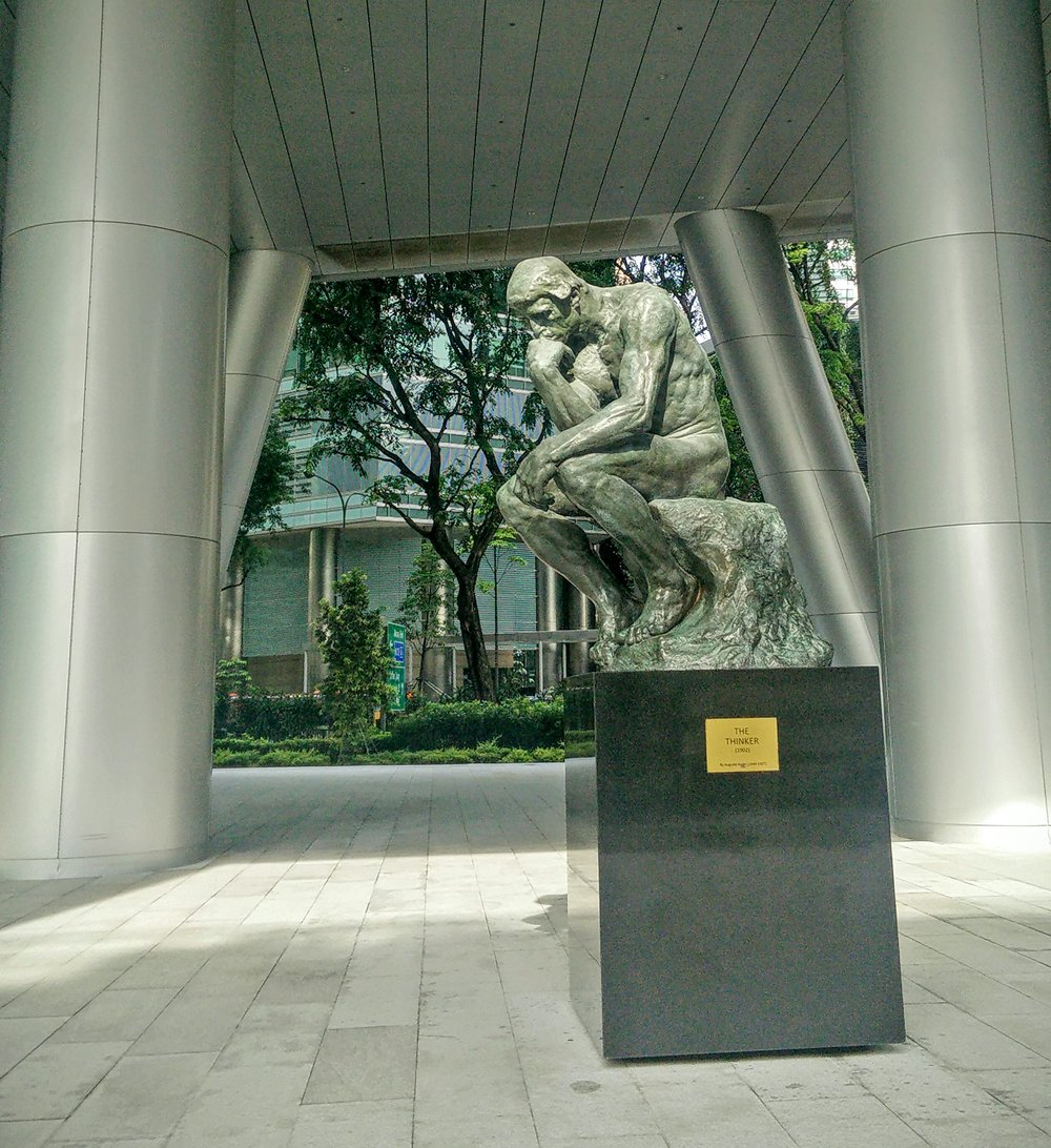 The thinker keeps thinking - a 1998 reproduction of the August Rodin classic is situated near a business / commercial center.