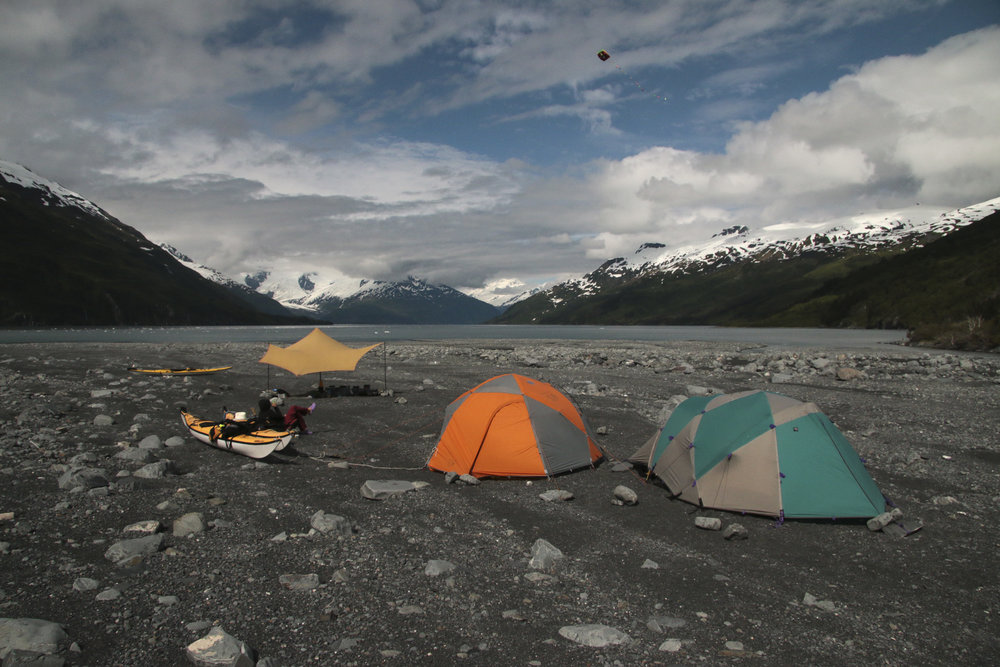 Once the weather cleared, the gravel field at the face of Harriman glacier was home for a few days. The tides are very high in the fjord so we parked our boats and made camp quite far from the water. Doubly smart since you never know when the glacier would calf, sending large waves your way. The winds off the glacier made for some cold camping (and bathing!), but also made for some great kite flying. Tied to a kayak, Pocket Kite stayed up all day. Here Barbara kicked back after a day of rangering.