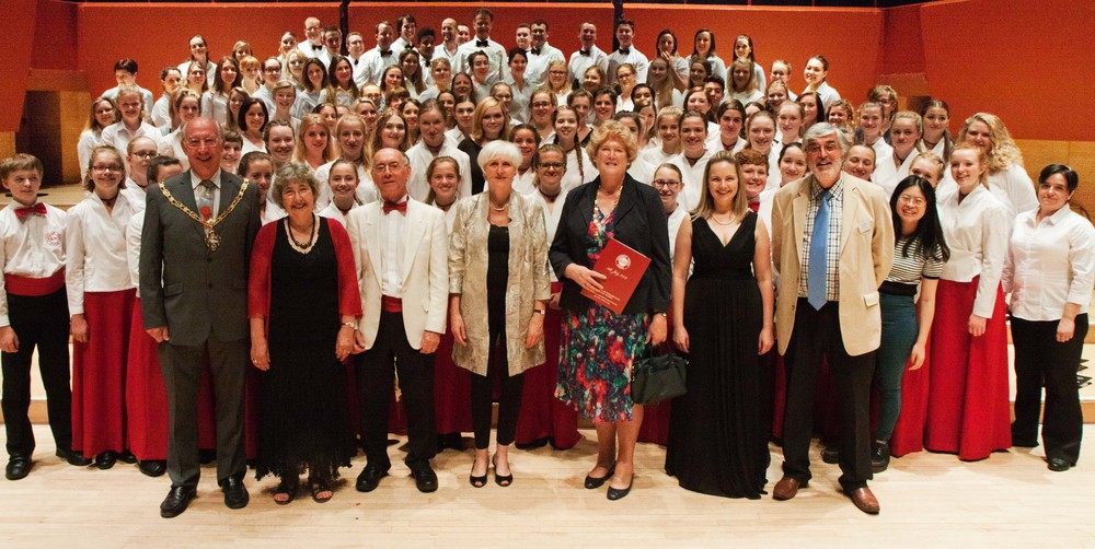 Farnham Youth Choir & Alumni Choir stand alongside the founders David & Gillian Victor-Smith (second and third left), accompanist Julia Freeman (centre), Choral Director - Joanna Tomlinson (second right) and FYC Chairman, Graham Noakes (right) at the Celebration Concert, The Anvil Basingstoke - July 2016.