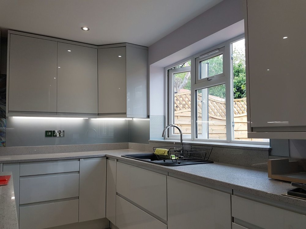 light grey acrylic splashbacks fitted to a full kitchen
