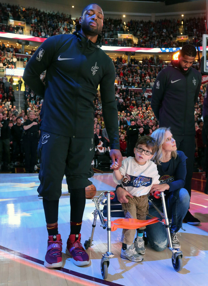 Dwyane Wade holds Ryan's hand during National Anthem (Photo: Gus Chan / The Plain Dealer)