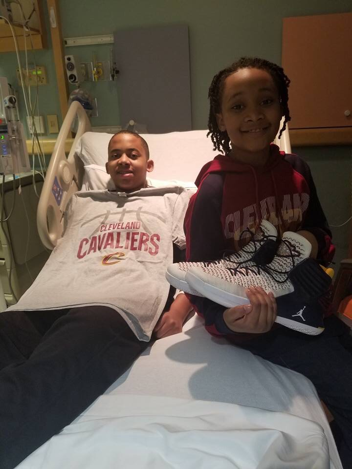 Jesiah (left) with brother Zion (right) as he holds Cavaliers player, Jeff Green's, shoes.