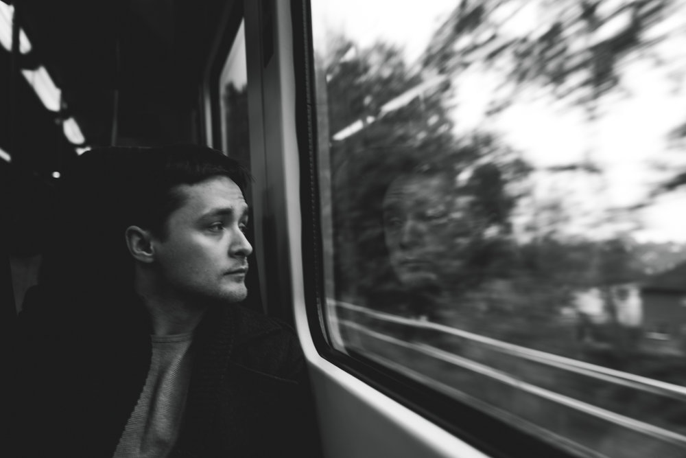 young man looking out the window of a moving train in black and white