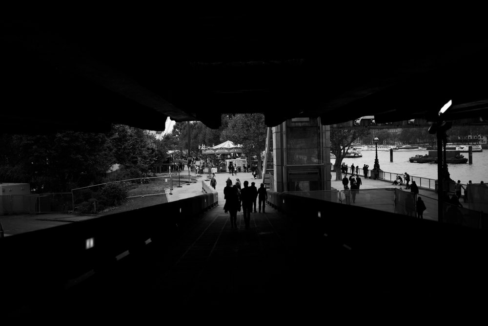 black and white photograph of london southbank with people walking away from the camera