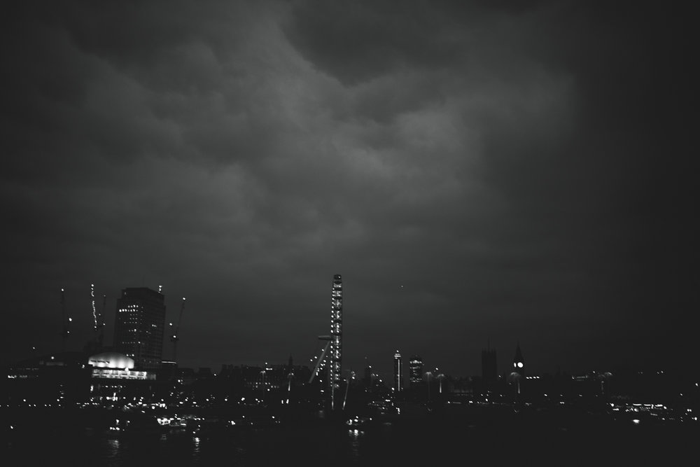 moody black and white london skyline with dark storm clouds and city lights